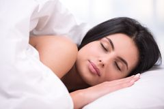 Young dark haired woman sleeping under a blanket Royalty Free Stock Photos