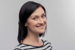 Young dark-haired woman smiling after hearing nice compliments. Smiling woman. Young dark-haired woman smiling after hearing nice compliments on image without royalty free stock images