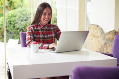 Young dark-haired woman working on laptop in cozy room with gard Royalty Free Stock Photo