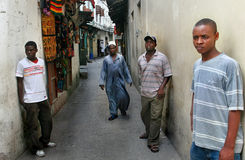 Young dark-skinned Africans stand near walls houses in Stone Tow. Zanzibar, Tanzania - February 16, 2008: Young African men standing along the walls of houses in royalty free stock photography