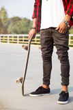 Young dark skinned man holding the skateboard Royalty Free Stock Photos