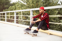 Young dark skinned man sitting with his skateboard. Picture of young dark skinned man wearing sunglasses and cap sitting with his skateboard. Against the nature Royalty Free Stock Photos