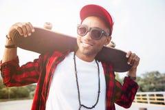 Young dark skinned man wearing sunglasses holding skateboard Royalty Free Stock Image
