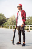 Young dark skinned man wearing sunglasses holding the skateboard Stock Photography