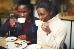 Young dark skinned man and woman drinking coffee while sitting together in modern cafe in cold winter day Royalty Free Stock Image