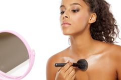 Decolletage - highlighter apply. Young dark skinned woman applying highlighter on her decolletage Royalty Free Stock Photography