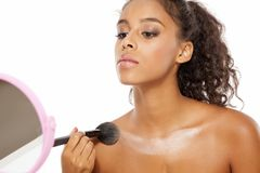 Decolletage - highlighter apply. Young dark skinned woman applying highlighter on her decolletage Royalty Free Stock Photo