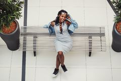Young dark-skinned woman dressed in casual clothes on the bench in the mall. Blurred background stock images