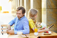 Young dating couple in the outdoor cafe. Young dating couple using smart phone and tablet pc in the outdoor cafe stock photos