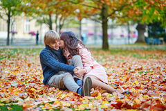 Young dating couple in Paris on a bright fall day. Sitting on the ground in autumn leaves royalty free stock photo