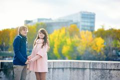 Young dating couple in Paris on a bright fall day. Walking together by the Seine, colorful autumn leaves in the background stock image