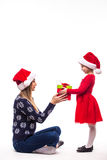 Young daughter in Christmas clothes give her mother Christmas gift Stock Photography