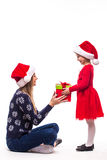 Young daughter in Christmas clothes give her mother Christmas gift Royalty Free Stock Image
