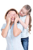 Young daughter closes hands eyes mom Stock Photography