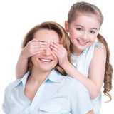 Young daughter closes hands eyes mom. Isolated. Happy family people concept royalty free stock images