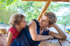 Young daughter embrace with her joyful mother and having fun. During a picnic on a wonderful summer evening. Happy mothers day in nature Stock Photos