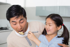 Young daughter feeding cereals to father in kitchen Stock Photography