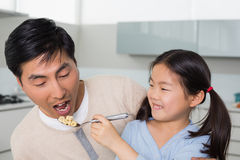 Young daughter feeding cereals to father in kitchen Royalty Free Stock Photos