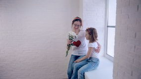 Young daughter gives mother flowers, hugging and loving. Loving family lifestyle. stock video footage