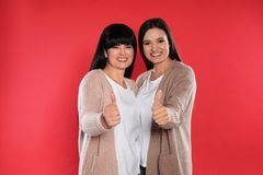 Young daughter and her mature mother showing thumbs up royalty free stock photos