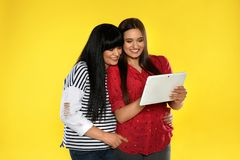 Young daughter and her mature mother with tablet computer royalty free stock photography