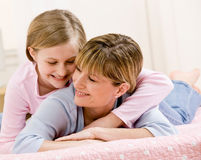 Young daughter hugging mother while lying on bed royalty free stock images