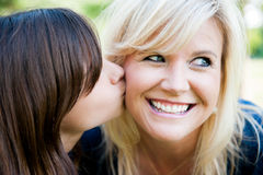Young daughter kissing mother's cheek. Young daughter kissing smiling mother's cheek oustide Royalty Free Stock Photos