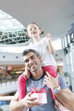 Young daughter sits on fathers shoulders Stock Images