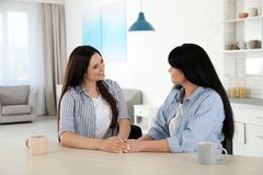 Young daughter speaking with her mature mother at table stock photo