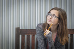 Young Daydreaming Female Student With Pencil Looking to the Side Stock Photo
