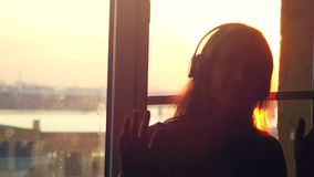 Young daydreaming woman sitting by the window wears headphones through the sun listen to music during amazing sunset stock video