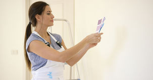 Young decorator deciding on a color of paint Royalty Free Stock Photo