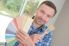Young decorator holding color samples and paint brush. Man royalty free stock photo