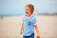 Young delighted boy, kid playing with a toy propeller, having fun on summer beach Royalty Free Stock Image