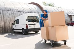 Delivery man with boxes on cart Stock Photos