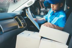 Young Delivery Man Checking Customer List On Clipboard. Stock Photography