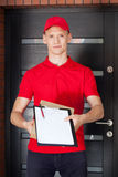 Young delivery man with clipboard and package Royalty Free Stock Photos