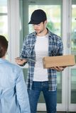 Young delivery man holding cardboard royalty free stock photos