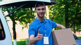 Young delivery man holding parcel, showing thumbs up, fast shipping service royalty free stock images