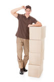 Young Delivery Man Leaning On A Stack Of Boxes Royalty Free Stock Photo