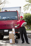 Young delivery man looking at delivery list on clipboard with truck in background Stock Images
