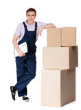 Young delivery man in overalls with cardboard boxes. Isolated on white. Transportation service Royalty Free Stock Photography