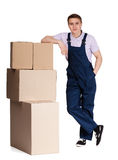 Young delivery man in overalls with pasteboard boxes. Isolated on white. Transportation service Royalty Free Stock Photo