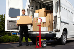 Young delivery man with parcel. Young delivery men with parcel near cargo truck. Shipping service Royalty Free Stock Images