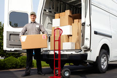Young delivery man with parcel. Young delivery men with parcel near cargo truck. Shipping service Stock Photos