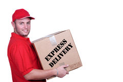 Young delivery man in red uniform holding the box. On white background royalty free stock photography