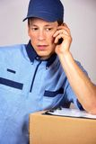 Young delivery man, speaking on the mobile Stock Photo
