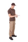 Young delivery man writing on clipboard royalty free stock images