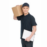 Young deliveryman at work.  Cheerful young deliveryman holding c Royalty Free Stock Images