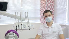 Young dentist sits in his office, next to dental setting. stock video